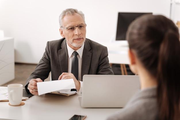 Professionele officemanager die informatie uit curriculum vitae controleert, glimlach op zijn gezicht zittend tegenover jonge vrouw