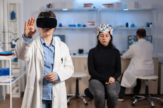 Professionele onderzoeker die een virtual reality-bril draagt met behulp van medische innovatie in het laboratorium dat de hersenscan van de patiënt analyseert. team van neurologische artsen die werken met een high-tech simulatorapparaat voor apparatuur.