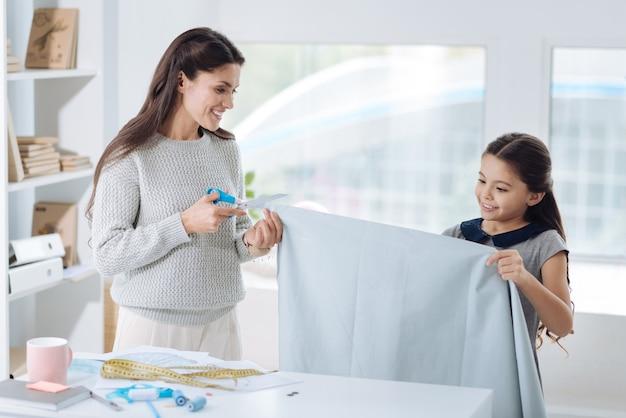 Professionele ontwerper. aangename aardige jonge vrouw die een schaar vasthoudt en een stuk stof afknipt terwijl ze wordt geholpen door haar dochter