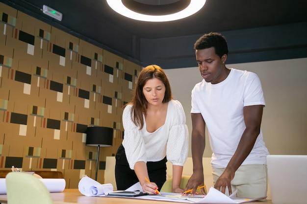 Professionele ontwerpers maken aantekeningen over tocht en staan in de buurt van een tafel in de coworking-ruimte