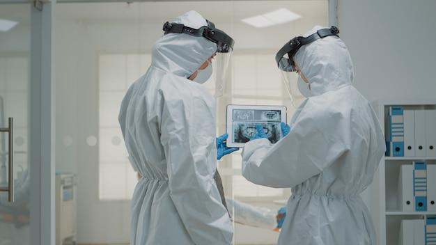 Professionele orthodontisten kijken naar tandheelkundige röntgenfoto's op digitale tablet