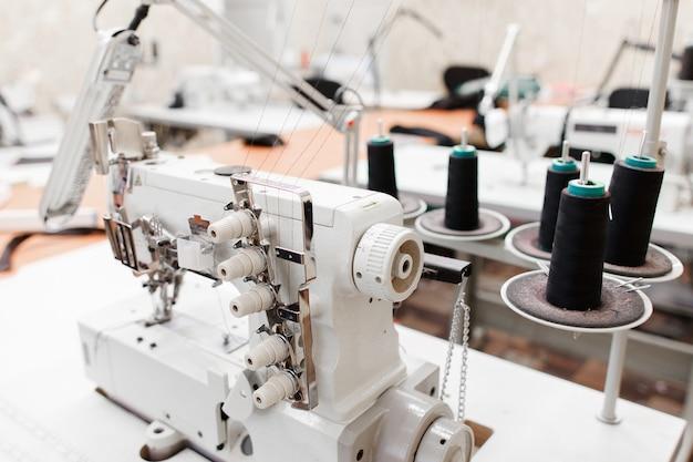 Professionele overlock naaimachine met zwarte draad in werkplaats.