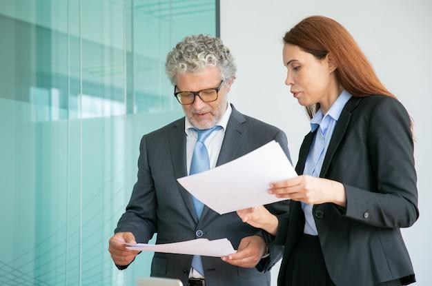 Professionele partners bespreken project en houden papieren in vergaderruimte