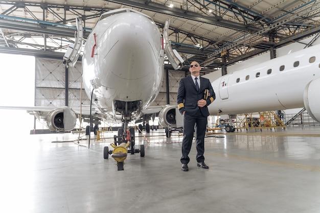 Professionele piloot die een pet in zijn handen houdt en naar de zijkant kijkt