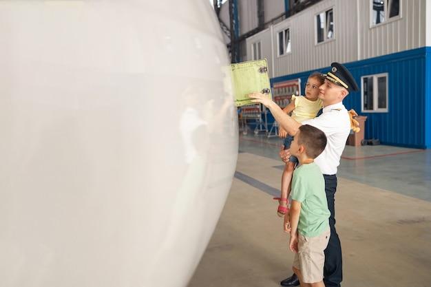 Professionele piloot in uniform die delen van een vliegtuig laat zien aan zijn twee kleine kinderen die hun vader kwamen bezoeken in de vliegtuighangar. vliegtuigen, familie, jeugdconcept