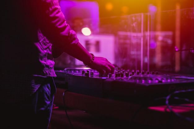 Professionele podiumgeluidsmixer close-up bij de hand van de geluidstechnicus met behulp van de schuifregelaar voor de audiomix die werkt tijdens concertuitvoeringen