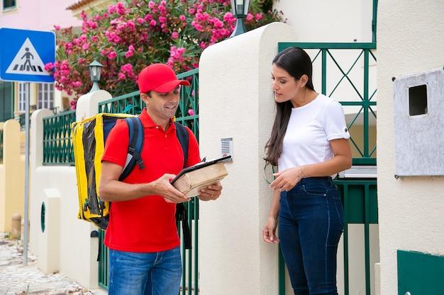 Professionele postbode leest ordergegevens voor aan klant. vrouw buitenshuis en luisteren man. koerier met klembord met thermische zak en pakket of pakket. bezorgservice en postconcept