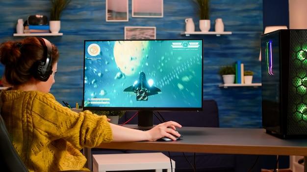 Professionele pro-gamer die space shooter-videogame speelt, nieuwe graphics op een krachtige computer vanuit huis