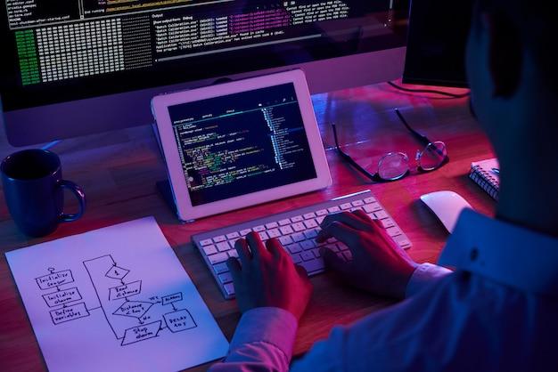 Professionele programmeur werkt laat in het donkere kantoor