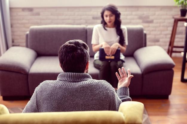 Professionele psycholoog. aardige knappe man die met zijn patiënt spreekt tijdens een psychologisch consult