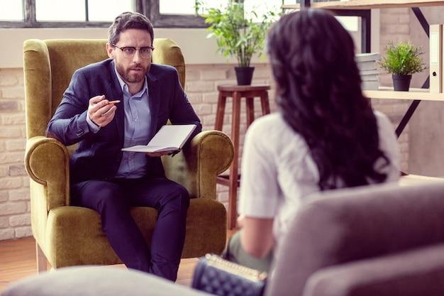 Professionele psycholoog. slimme knappe man die naar zijn patiënt kijkt terwijl hij het probleem aan haar uitlegt