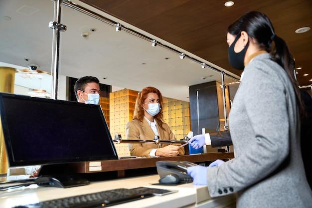 Professionele receptionisten en hotelgasten die de veiligheidsmaatregelen in acht nemen en communiceren in medische maskers