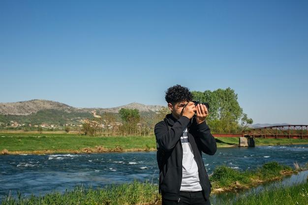 Professionele reizigerfotograaf die foto van aard nemen