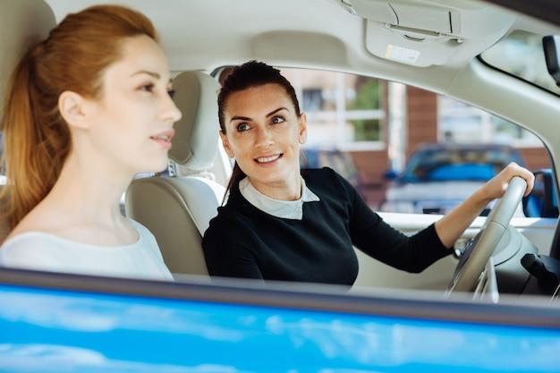 Professionele relaties. positieve leuke aantrekkelijke zakenvrouw zit achter het stuur en kijkt naar haar collega terwijl ze met haar gaat werken