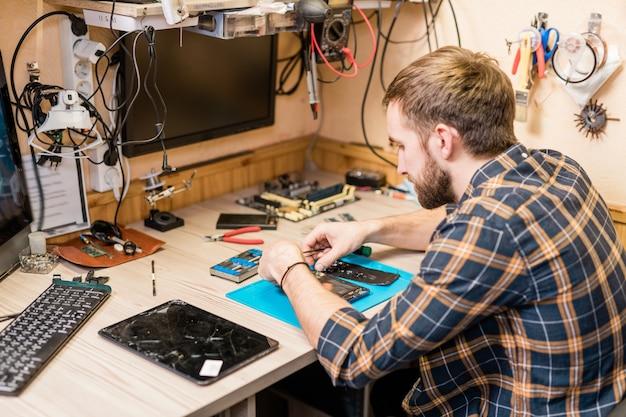 Professionele reparateur met een pincet die over gebroken smartphone buigt en kleine onderdelen of bouten per werkplek bevestigt
