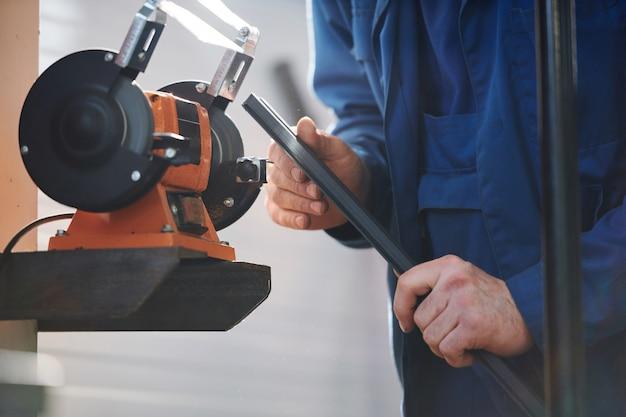 Professionele reparateur of technicus in blauw uniform die het werkstuk van de staaf vasthoudt terwijl hij door een metaalverwerkingsmachine staat