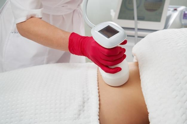 Professionele schoonheidsspecialist die radiofrequente tilprocedure op de buik van een vrouw uitvoert