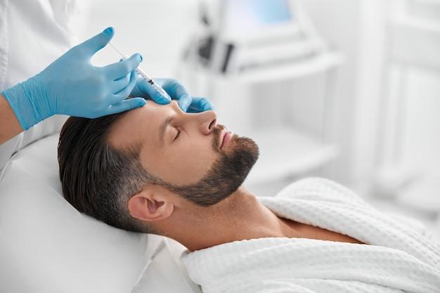 Professionele schoonheidsspecialist doet injectie bij wenkbrauwliftprocedure om de man in de kliniek te laten rijpen