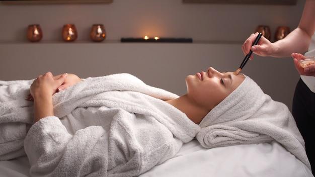 Professionele schoonheidsspecialiste cosmetische masker toe te passen op vrouwelijk gezicht in de schoonheidssalon. vrouw heeft cosmetische behandeling in spa salon.