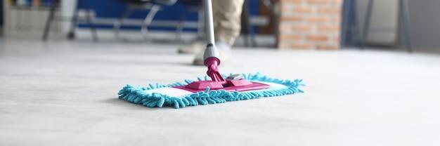 Professionele schoonmaakdiensten voor complexe schoonmaak van gebouwen. man wassen vloer mop met vochtige doek binnenshuis.