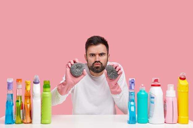 Professionele schoonmaakservice. boos bebaarde man houdt twee sponzen vast, trekt een grimas, heeft een norse uitdrukking, draagt witte kleren