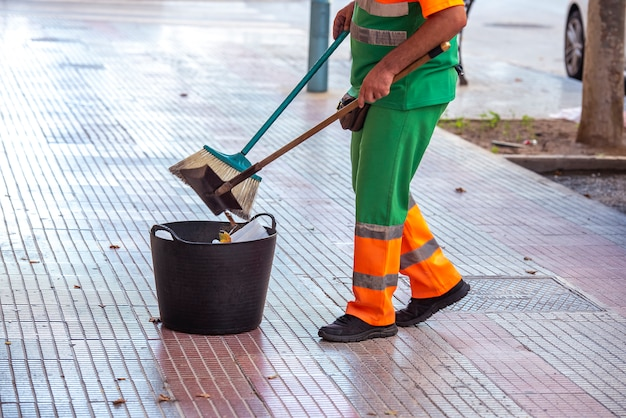 Professionele schoonmaker veegt de straten van de stad, met een mand om het afval dat hij verzamelt weg te gooien