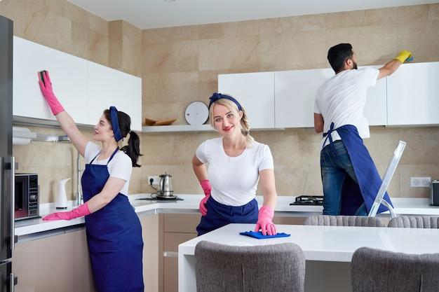 Professionele schoonmakers in blauw uniform wassen vloer en stof van het meubilair in de woonkamer van het appartement vegen. schoonmaak dienstverleningsconcept