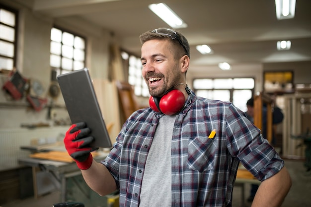 Professionele schrijnwerker met behulp van tablet in timmerwerkplaats