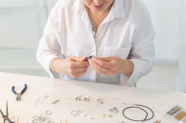 Professionele sieradenontwerper die handgemaakte sieraden maakt in de close-up van de studioworkshop. mode, creativiteit en handgemaakt concept