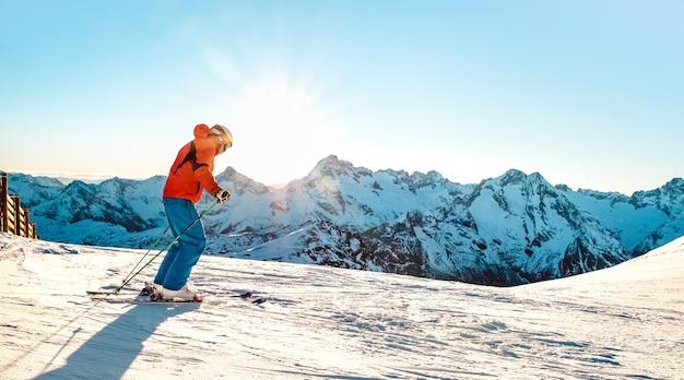 Professionele skiër atleet skiën bij zonsondergang bovenop de franse alpen