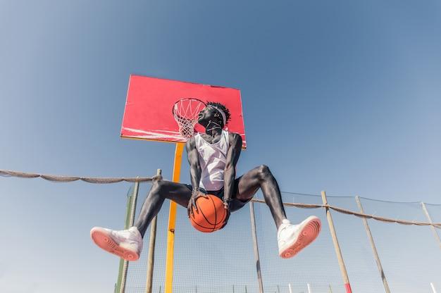 Professionele slam dunk. basketbalspeler die een achterste slag dompelt.