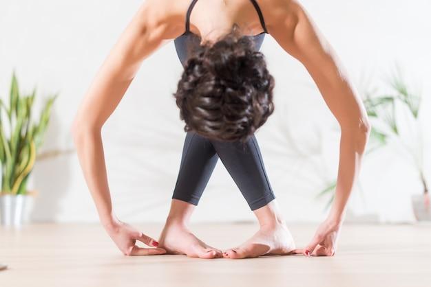 Professionele slanke brunette balletdanser die zich voordeed op lichte achtergrond in de studio. jonge vrouw die uitrekkende buigende oefening doet