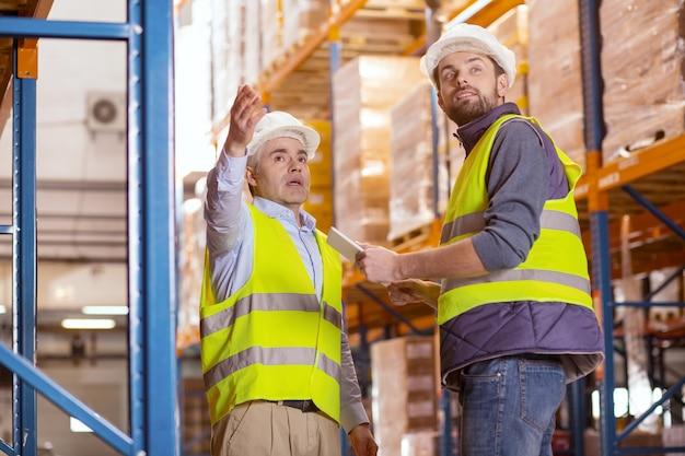 Professionele slimme mannen staan samen tijdens het bespreken van werkproblemen in het magazijn