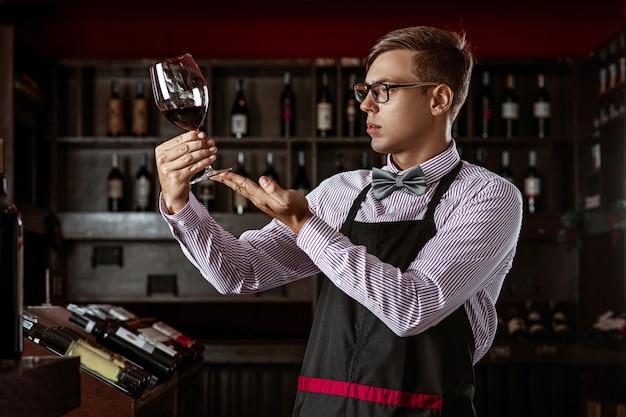 Professionele sommelier die naar de kleur van rode wijn kijkt