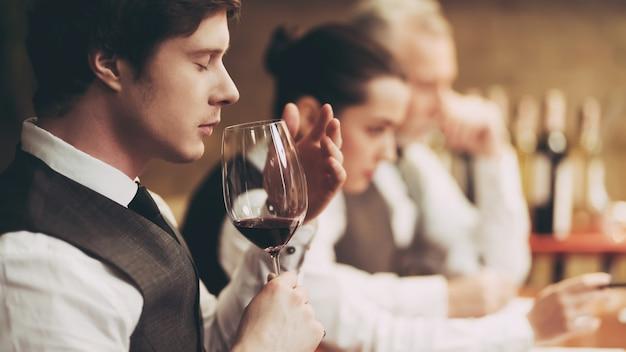 Professionele sommelier smaakt rode wijn in restaurant.