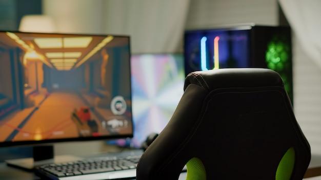 Professionele speelkamer met niemand erin, neonlichten en krachtige rgb-computer, toetsenbord en muis. fps shooter-videogame op pc-display, studio van esport, fps-shooter-videogame