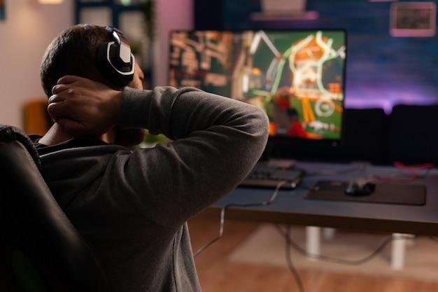 Professionele speler die shooter-videogame nieuwe graphics speelt op een krachtige computer vanuit huis. virtuele online streaming cyberprestaties tijdens gametoernooien met behulp van draadloos technologienetwerk