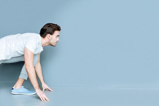 Professionele sportman. ernstige aardige atletische man die uitkijkt en zich voorbereidt om te rennen terwijl hij deelneemt aan de sportcompetitie