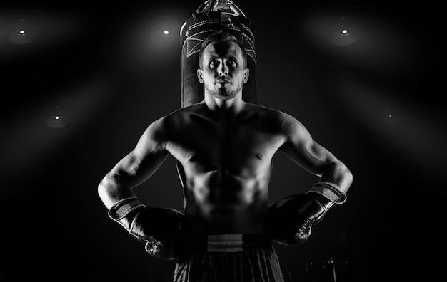 Professionele sportman van mixed martial arts staat na het gewonnen gevecht in de buurt van de tas en kijkt dreigend naar zijn volgende tegenstander.
