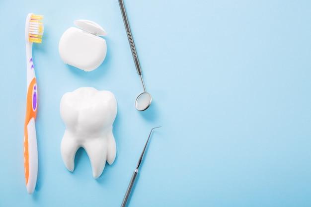 Professionele stalen tandheelkundige instrument met een spiegel in de buurt van witte tand model, tandenborstel en flosdraad op lichtblauwe tafel