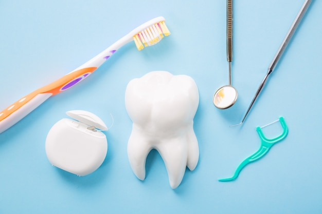 Professionele stalen tandheelkundige instrument met een spiegel in de buurt van witte tand model, tandenborstel en tandzijde op lichtblauwe achtergrond.