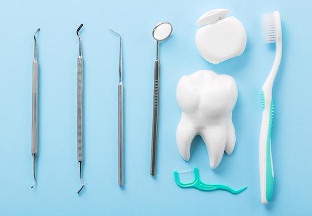 Professionele stalen tandheelkundige instrumenten met een spiegel in de buurt van witte tand model, tandenborstel en flosdraad op lichtblauwe tafel.