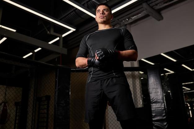 Professionele sterke mannelijke bokser in bokshandschoenen staat in pose klaar om te vechten op de ring, voor of na het vechten. kickboks concept.