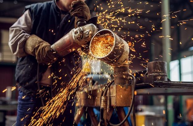 Professionele stof werknemer in beschermende uniforme metalen pijp snijden op de werktafel met een elektrische slijper in de industriële werkplaats.