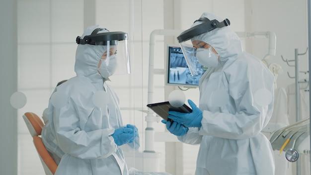 Professionele stomatologen die digitale tablet in tandkabinet gebruiken