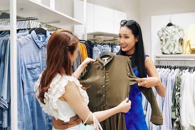 Professionele stylist die met de klant werkt en haar helpt bij het kiezen van de beste kleding in de winkel
