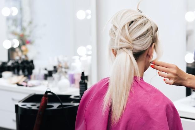 Professionele stylist doet het haar van een blond meisje