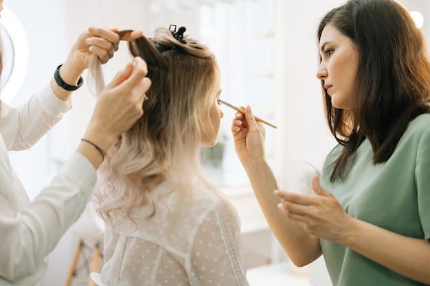 Professionele stylist en visagist doen make-up en stylen haar voor jonge vrouw