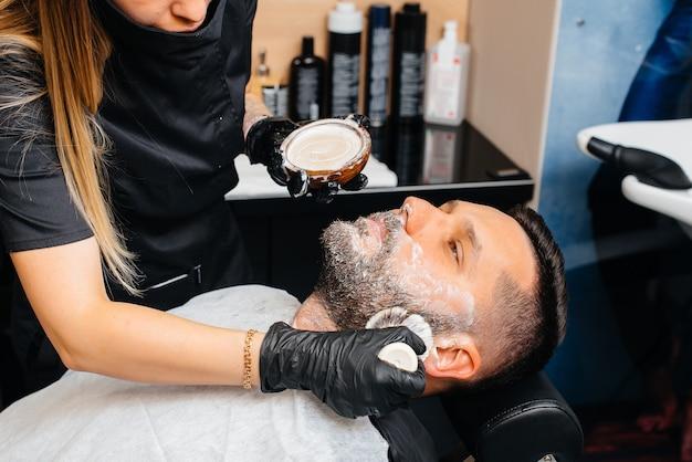 Professionele stylist in een moderne, stijlvolle kapperszaak scheert en knipt het haar van een jonge man