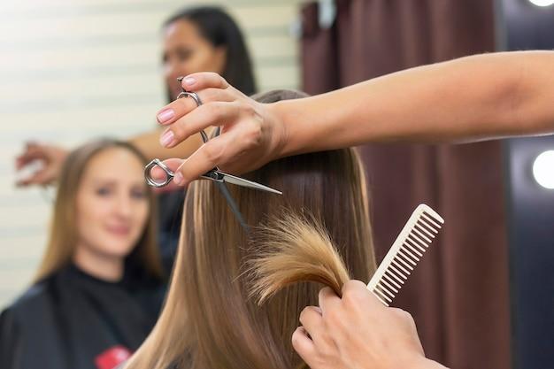 Professionele stylist knipt vrouwelijk haar in salon